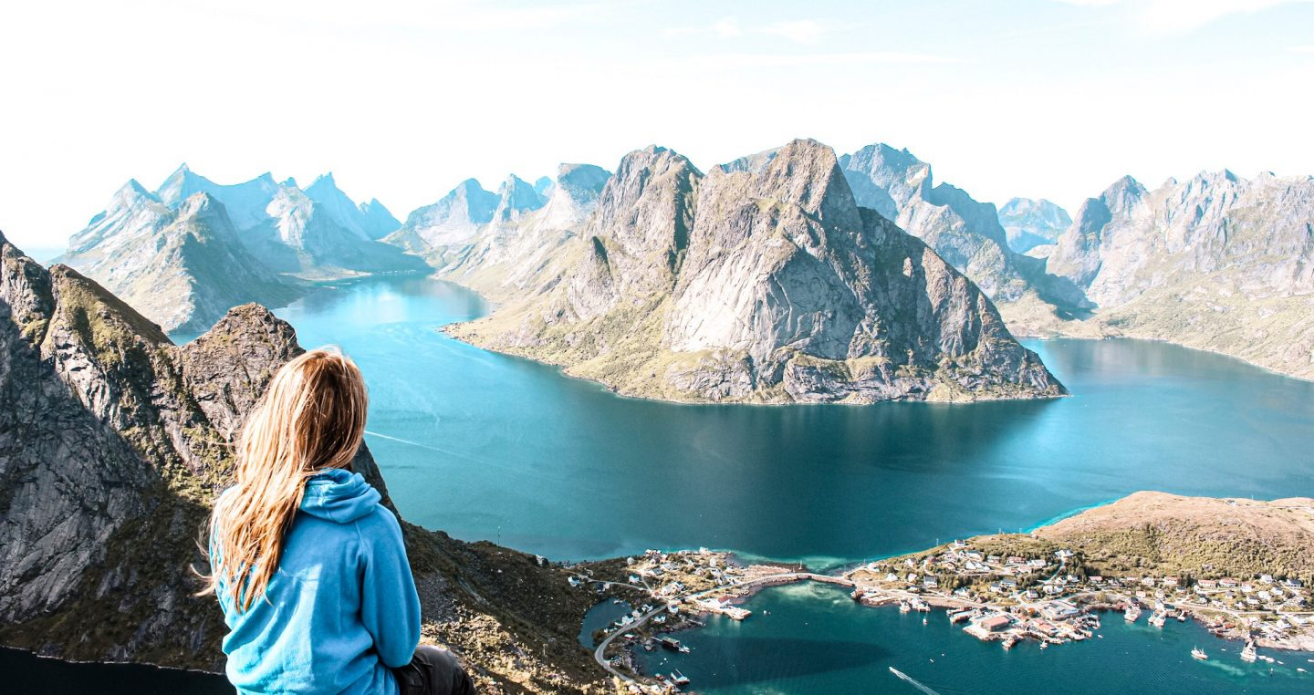 Woman sitting on a mountain looking down to a lake! Female solo traveler